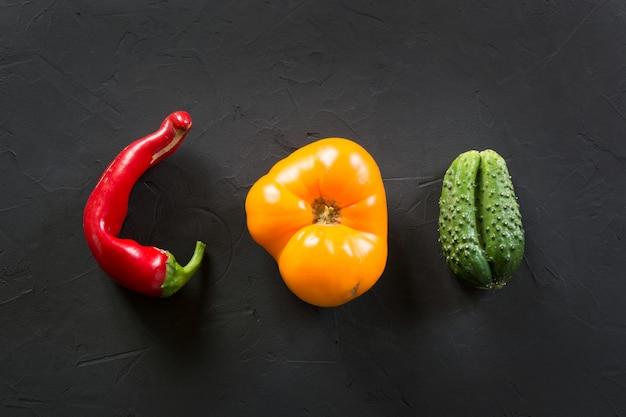 Hässliche organische bunte tomate, pfeffer, gurke auf schwarzem.