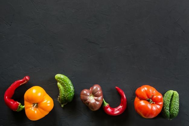 Hässliche organische bunte tomate, pfeffer, gurke auf schwarzem,