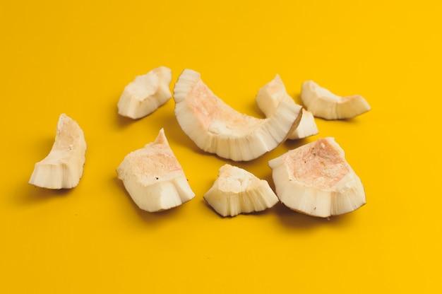Hässliche organische gebrochene faule kokosnuss auf leuchtendem gelb.