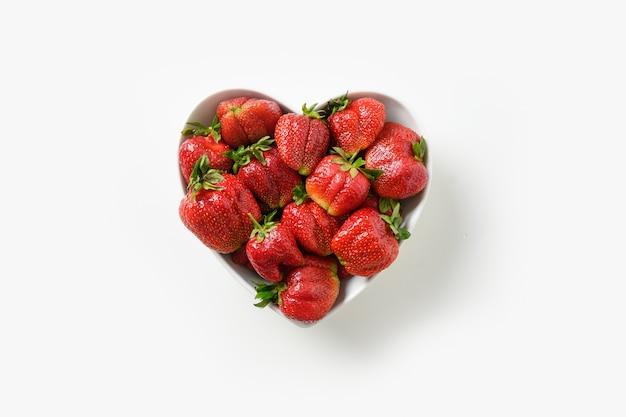 Hässliche reife bio-erdbeere auf weißem hintergrund