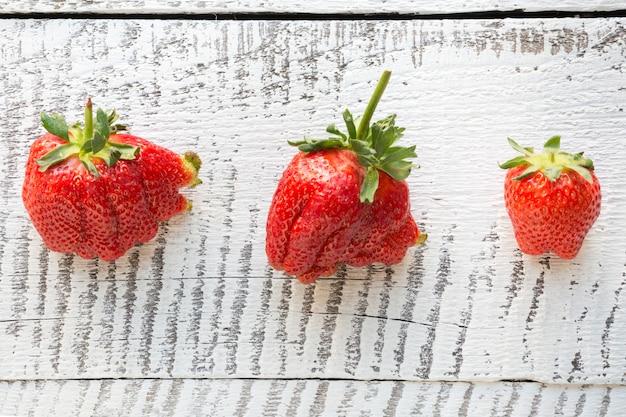 Hässliche reife organische erdbeere drei lokalisiert