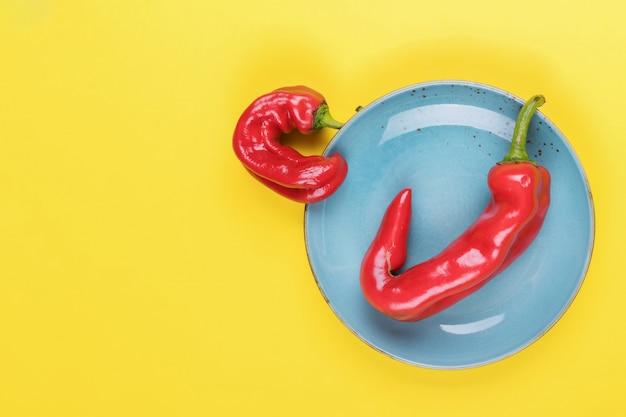 Hässliche rote paprikapfeffer auf einer türkisplatte auf einer gelben, minimalen art der natur, pop-art, kreatives lebensmittel, moderne kunst