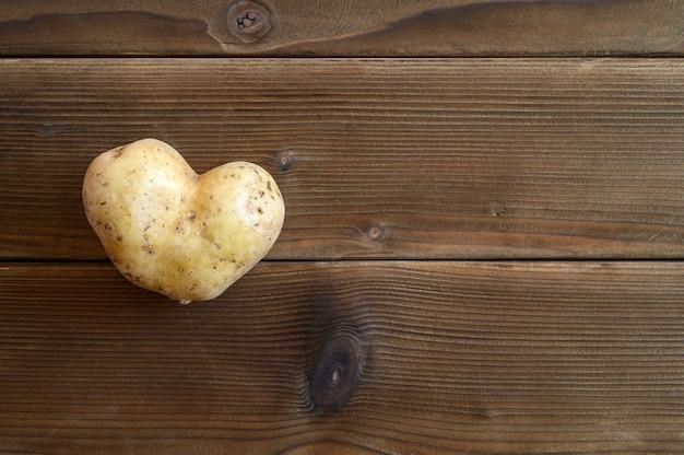 Hässliches essen. ein hässliches gemüse eine herzförmige kartoffel auf einem holztisch. platz für text