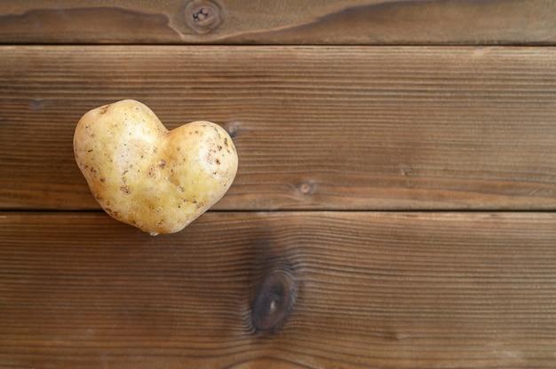 Hässliches essen. ein hässliches gemüse eine herzförmige kartoffel auf einem holztisch