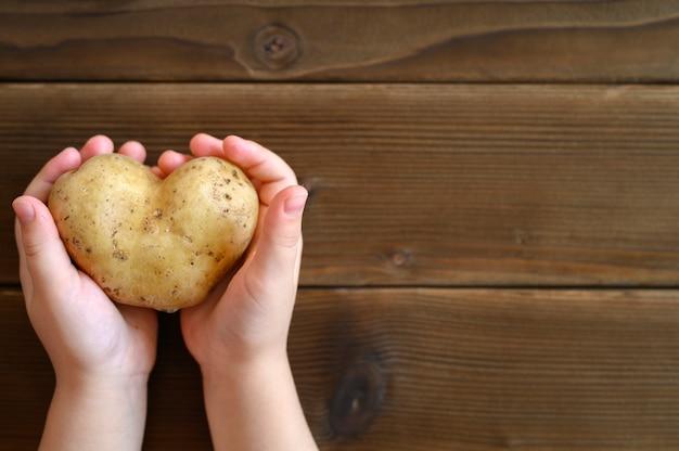Hässliches essen. kinderhände halten hässliches gemüse eine herzförmige kartoffel auf einem hölzernen plankentisch.