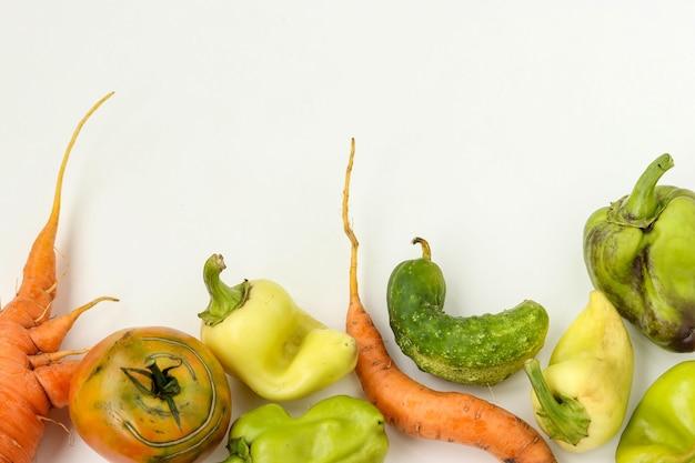 Hässliches gemüse: karotten, gurken, paprika und tomaten auf weißem hintergrund, hässliches lebensmittelkonzept, horizontales foto, kopierraum