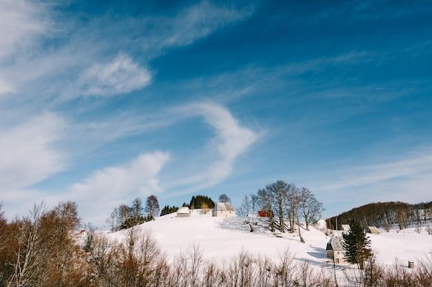 Häuser im norden montenegros auf einem hügel zwischen den bäumen im winter auf dem schnee vor blauem himmel