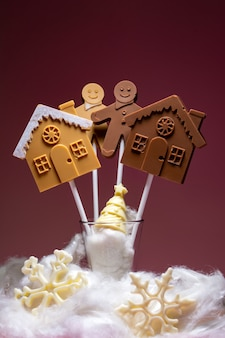 Häuser und menschen aus schwarz- und milchschokolade am stiel