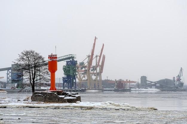 Hafenlandschaft mit leuchtturm und containerkränen an einem kalten, nebligen wintermorgen, riga, lettland