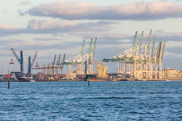 Hafentransportkran und -behälter über dem hintergrund des blauen himmels, bereiten für versand vor