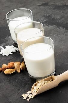 Hafer des strengen vegetariers, mandel, kokosmilch im glas auf einem dunklen hintergrund. milch ohne milch