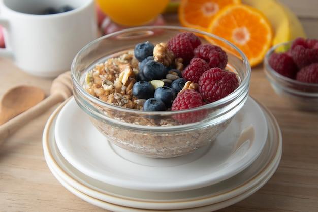 Hafer, müsli und verschiedene köstliche früchte, beeren zum frühstück.