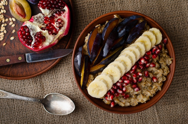 Haferbrei, banane, granatapfelkernen und pflaumen auf sackleinen