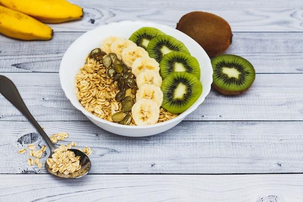 Haferbrei mit banane, kiwi und samen für gesundes frühstück auf holztisch.
