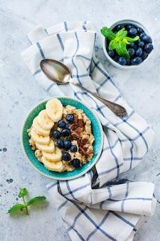 Haferbrei mit banane, schokolade und frischer blaubeere in einer schüssel auf einer hellgrauen schiefer-, stein- oder betonoberfläche