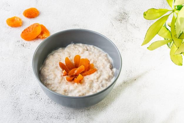 Haferbrei oder haferbrei hafer oder frühstückszerealien mit getrockneten aprikosen isoliert auf weißem marmor hintergrund. hausgemachtes essen. leckeres frühstück. selektiver fokus. horizontales foto.