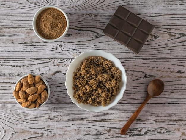 Haferbrei und quinoa und kakao mit zutaten auf einem holztisch. gesunde ernährung. flach liegen.