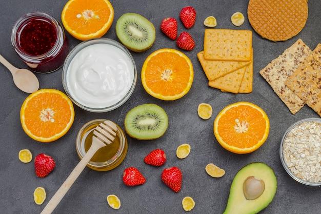Haferflocken, avocado-beeren, obst, marmelade, joghurt für ein gesundes frühstück.
