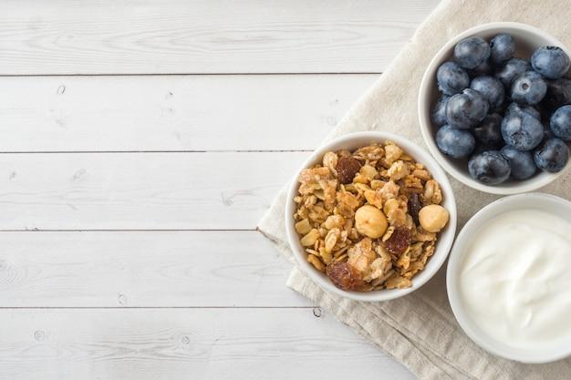 Haferflocken, granulat und nussmüsli mit heidelbeeren. das konzept der gesunden ernährung, frühstück.