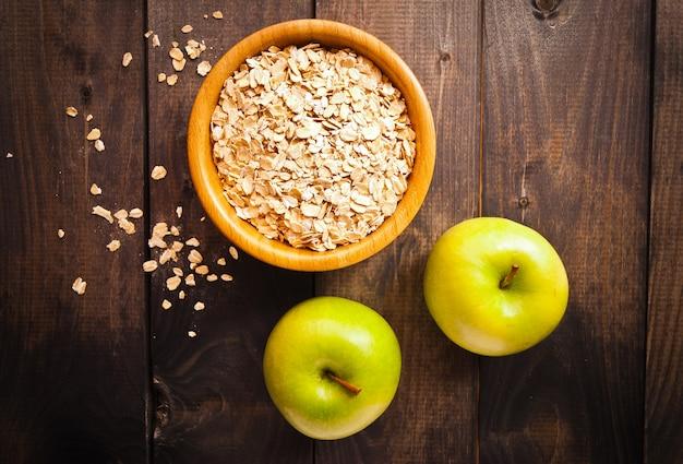 Haferflocken in der schüssel und in zwei äpfeln