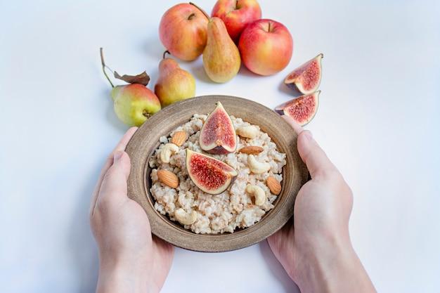 Haferflocken in einer schüssel mit frischen feigen, mandeln und cashewnüssen haferflocken mit früchten. männerhände halten eine schüssel brei. weiß .