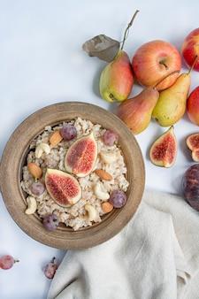 Haferflocken in einer schüssel mit frischen feigen, mandeln und cashewnüssen haferflocken mit früchten. weiß .