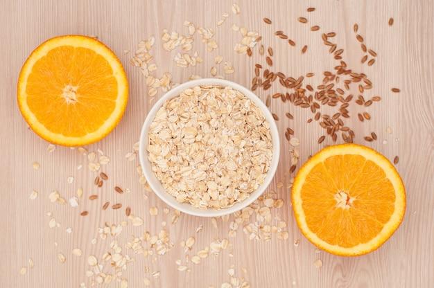 Haferflocken in einer weißen schüssel und halbierte orangen auf einem hölzernen hintergrund zum frühstück