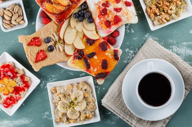 Haferflocken in tellern mit früchten, marmelade, nüssen, obstsandwich, kaffee