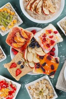 Haferflocken in tellern mit früchten, marmelade, nüssen, zimt, früchten