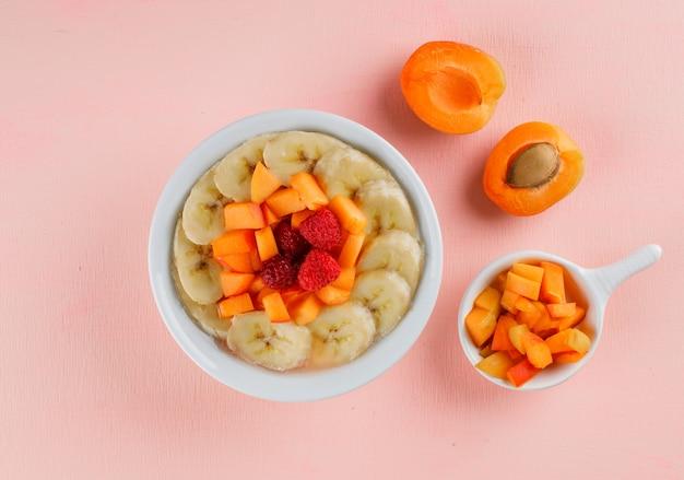 Haferflocken mit aprikose, banane, beeren in einer schüssel
