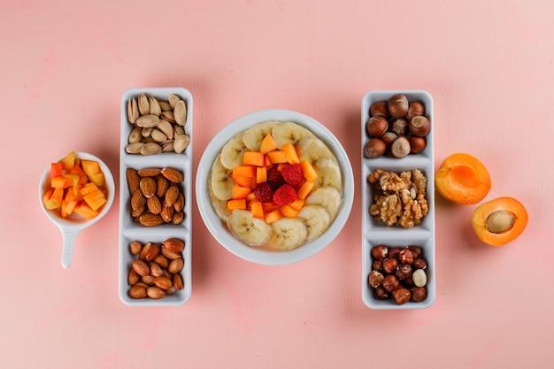 Haferflocken mit banane, aprikose, beeren, nüssen in einer schüssel