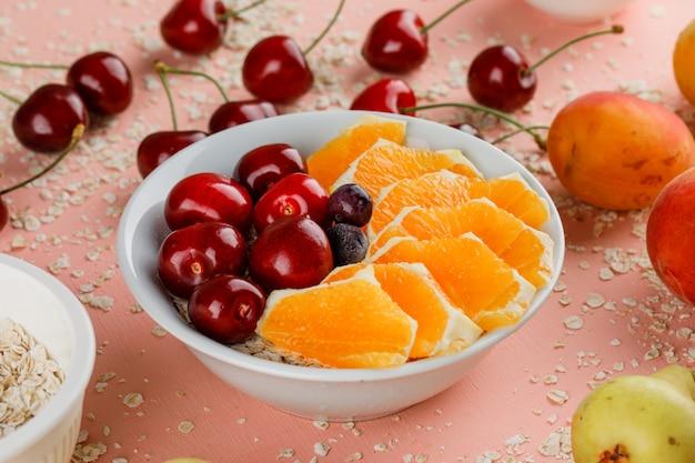Haferflocken mit birne, aprikose, orange, kirsche, beeren in schüssel