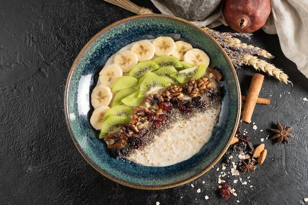 Haferflocken mit chiasamen, banane, kiwi, walnüssen und getrockneten preiselbeeren.