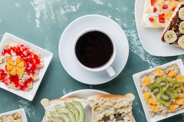 Haferflocken mit früchten, marmelade, sandwich, kaffee in tellern