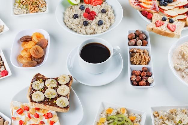 Haferflocken mit früchten, nüssen, kaffee, obstsandwich, trockenen aprikosen in tellern