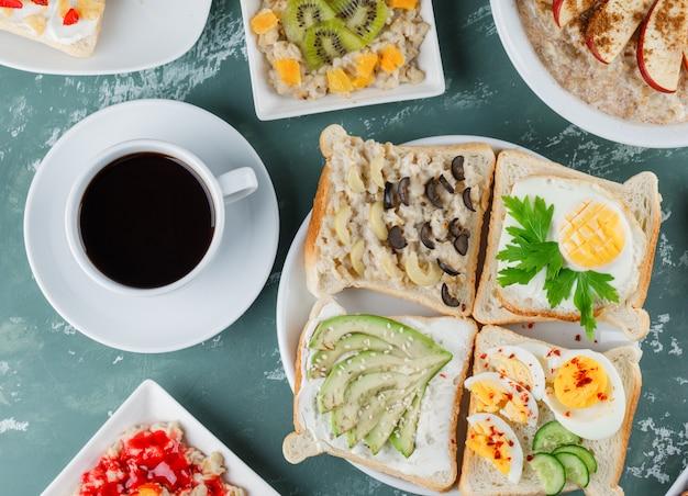 Haferflocken mit früchten, zimt, marmelade, sandwich, kaffee in tellern