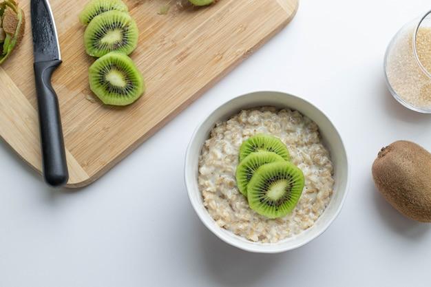 Haferflocken mit kiwi und honig in weißer schüssel auf einem leckeren und gesunden frühstück