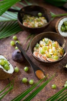 Haferflocken mit kokosnuss, stachelbeerbeeren, karamellsauce und feigen