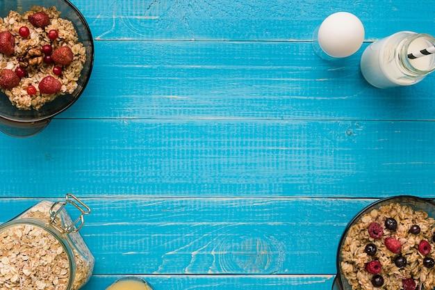 Haferflocken mit milch und beeren schüssel mit löffel auf blauem hintergrund aus holz. gesundes essen zum frühstück. ansicht von oben. platz kopieren