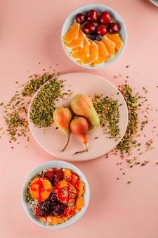 Haferflocken mit pistazien, früchten, teller, gelee in schalen