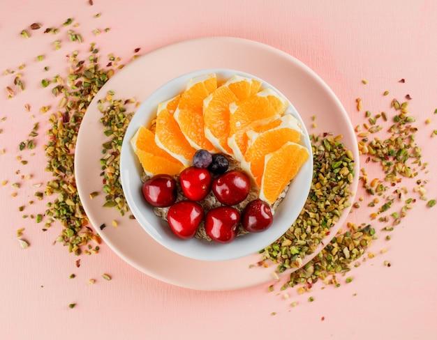 Haferflocken mit pistazien, kirschen, orangen, beeren, teller in einer schüssel