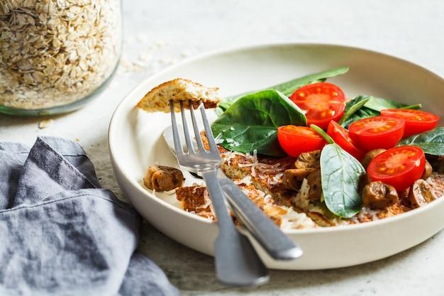 Haferflocken-omelett-pfannkuchen mit käse, pilzen, tomaten und spinat. gesundes fitnessfrühstück.