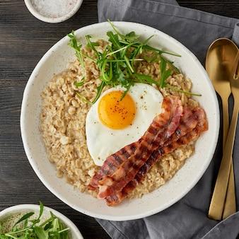 Haferflocken, spiegelei und gebratener speck. brutales mann-sportfrühstück. herzhaftes fettes frühstück. makro