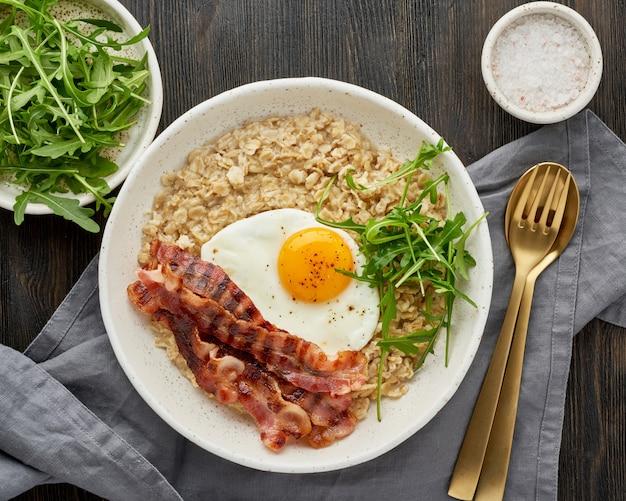 Haferflocken, spiegelei und gebratener speck. brutales mann-sportfrühstück. herzhaftes fettreiches kalorienreiches frühstück,