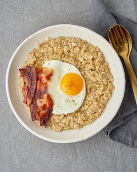 Haferflocken, spiegelei und gebratener speck. herzhaftes, fettreiches, kalorienreiches frühstück, energiequelle.