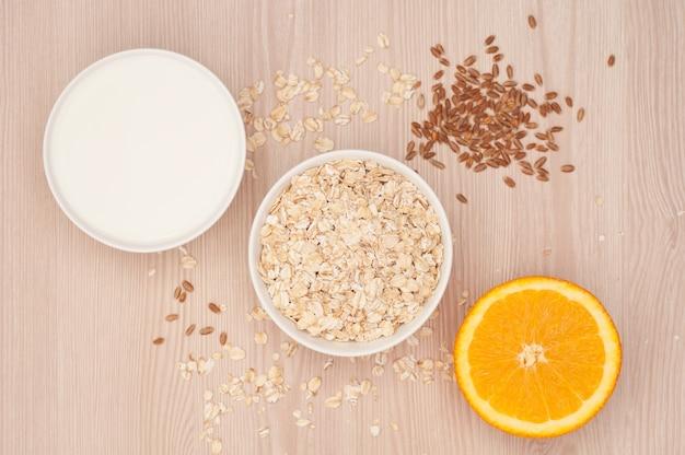 Haferflocken und milch in einer weißen schüssel und eine halbe orange zum frühstück