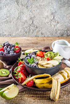 Haferflocken zum frühstück. morgenhaferflocken mit verschiedenen früchten und beeren, auf rustikalem holzhintergrund-kopierraum
