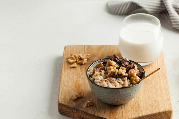 Haferflockenbrei mit nussschokolade in einer grauen schüssel ein glas milchfrühstück gesunder foodcopy space...
