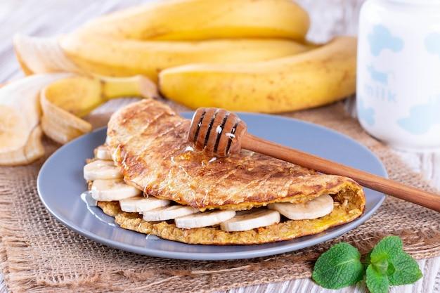 Haferflockenpfannkuchen mit banane und honig auf teller