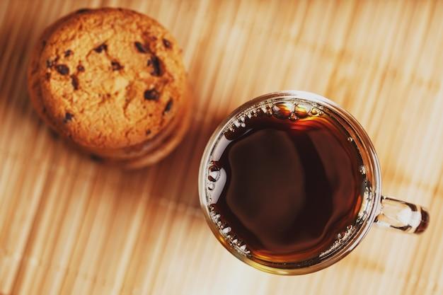 Haferflockenplätzchen mit schokoladenstücken und einer tasse aromatischem schwarzem tee herein auf einem bambussubstrat